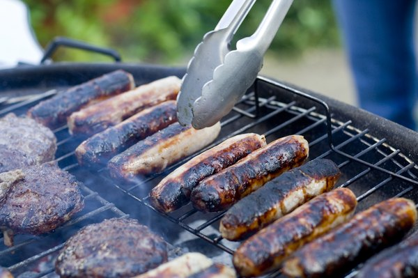 Close-up of tongs being used to handle sausages on a BBQ grill