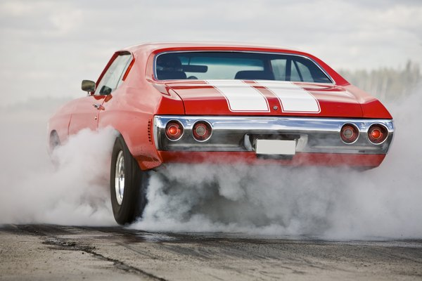 A red muscle car burning rubber