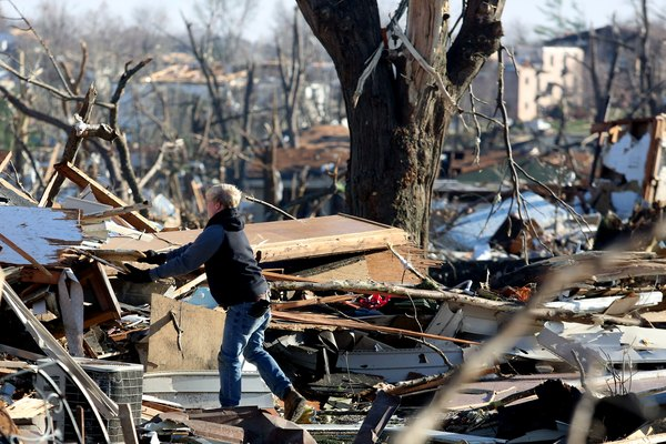 A person sorts through the debris after a tornado strikes.
