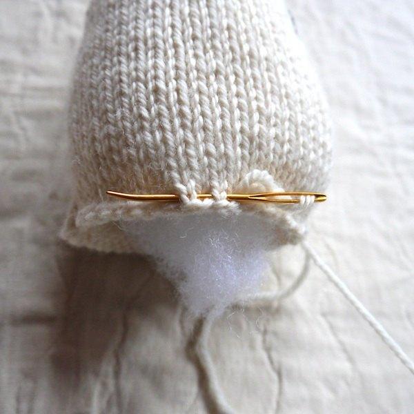 Passe a lã branca ao redor do fundo da cabeça