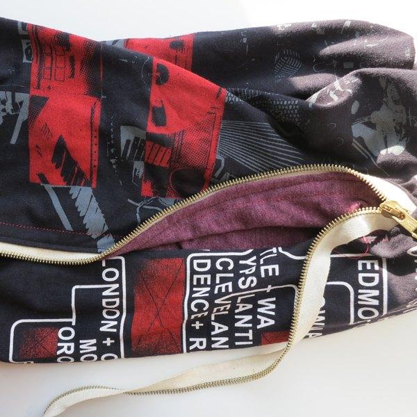 Costure o zíper, a mochila e o forro da mochila