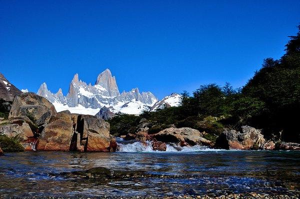Panorámica de una montaña nevada y un arroyo en la Patagonia Argentina.
