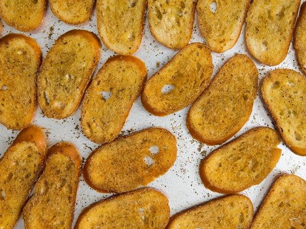 Pon las tostadas en el horno con aceite de oliva, sal y, si quieres, un poco de orégano.