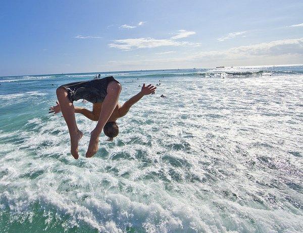 Un niño se arroja al mar en las playas de Hawaii.