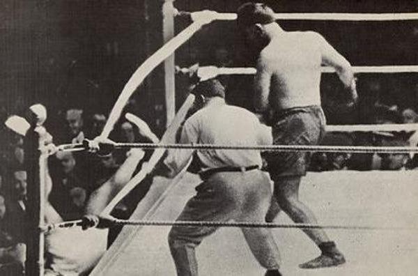 Imagen de Dempsey cayendo afuera del cuadrilátero tras un certero golpe de Firpo