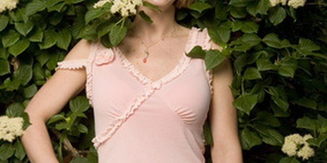 A young woman standing in front of climbing hydrangea vines.