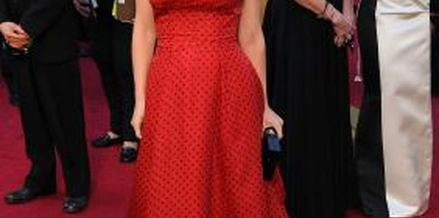 Actress Natalie Portman wears a red dress and diamond necklace to the 2012 Academy Awards.