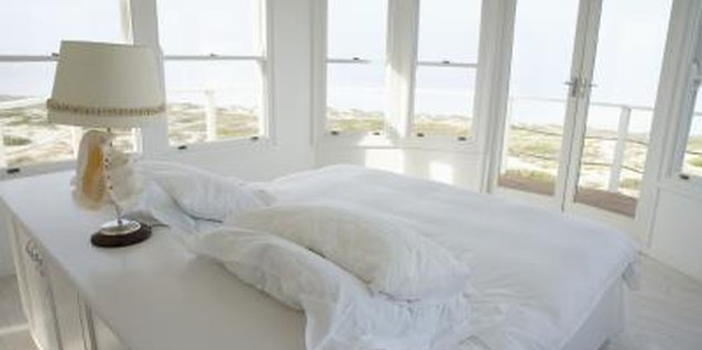 Float the bed, hiding the back with a table, to avoid blocking any windows.