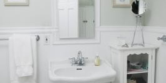 White furnishings and fixtures help to brighten gray bathroom walls.