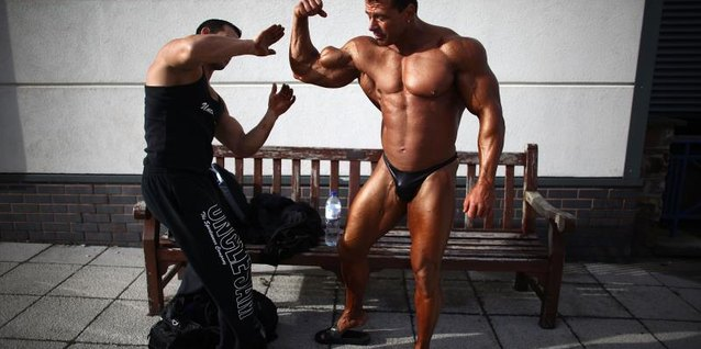 A bodybuilder has fake tan applied to him before a competition.