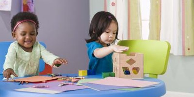 Toddlers play side by side without much interaction during parallel play.