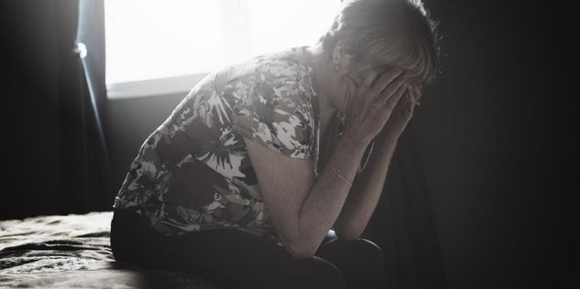 A middle-aged woman sits on the edge of a bed in a motel room, holding her head in her hands.