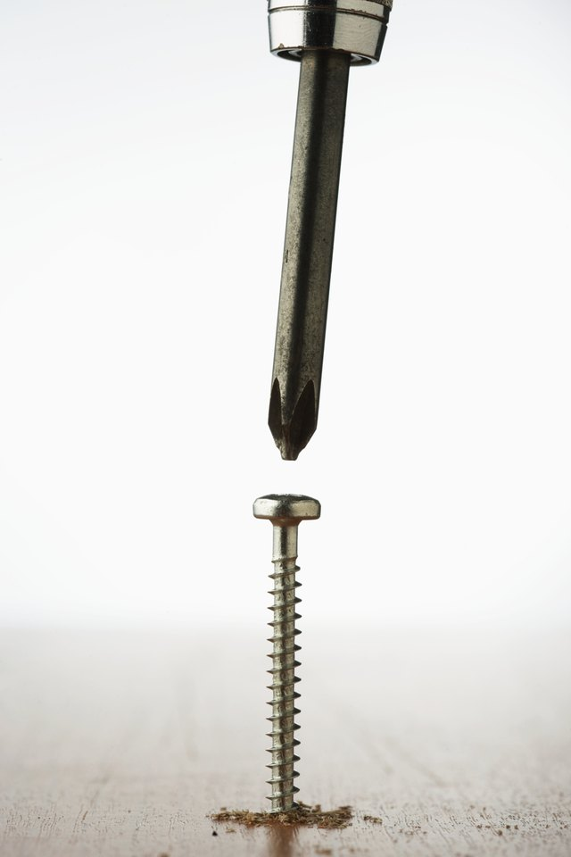 Crosshead screwdriver above screw sticking out of wood, close-up