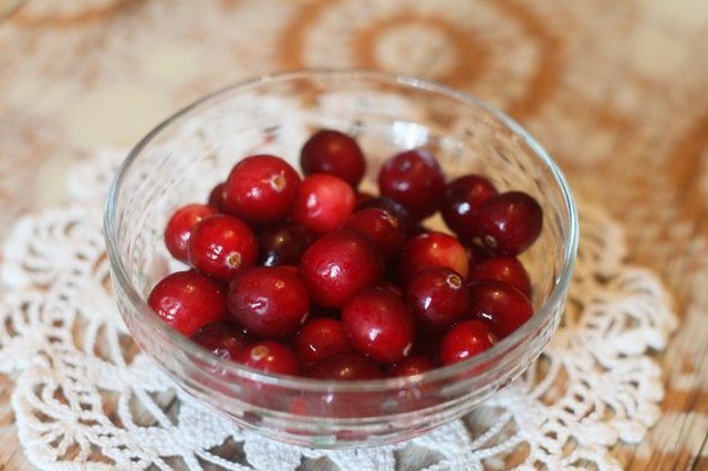 A small glass bowl of whole cranberries on a crocheted white toily