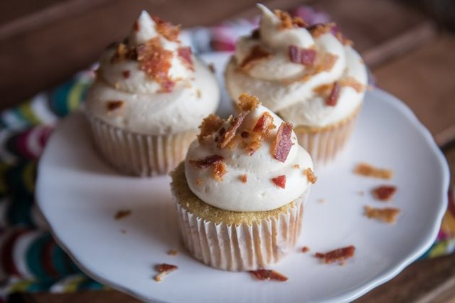 Cupcakes on a white plate, mounded with off-white frosting and sprinkled with crumbled bacon bits