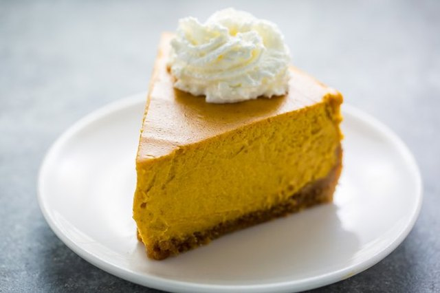 A thick wedge of pumpkin cheesecake with a whipped cream rosette on top, served on a white plate and a light-grey counter