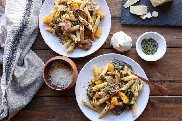 Overhead shot of two white plates of penne with squash and sausage on a rustic table, surrounded by the dish's ingredients and a clean kitchen towel