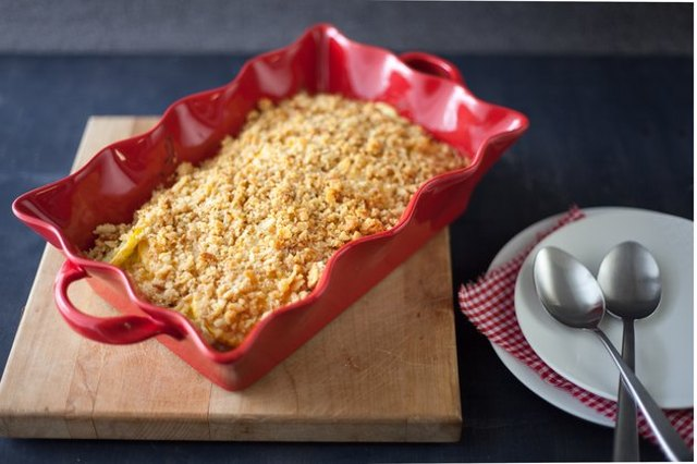 Squash casserole in a red fluted baking dish, displayed on a wooden cutting board alongside white side plates and spoons