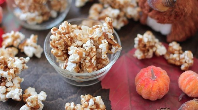 Pumpkin spice caramel corn in and around a small glass bowl, with miniature pumpkins alongside