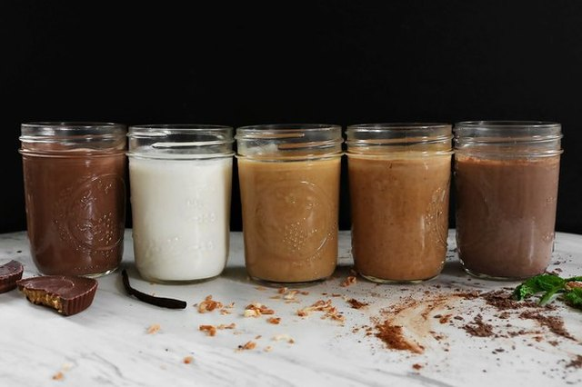 A row of homemade coffee creamers in different flavors, served in mason jars, and with flavoring ingredients scattered around them on a white tablecloth