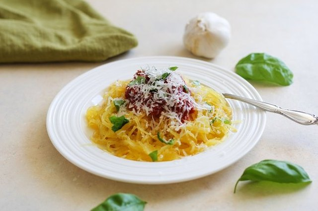 A serving of spaghetti squash topped with tomato sauce, basil and parmesan, in a white pasta bowl surrounded by bay leaves and a bulb of garlic
