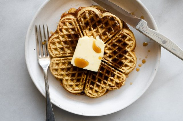 Waffles made in a decorative iron, shot from overhead, on a white plate with a pat of butter, syrup, knife and fork