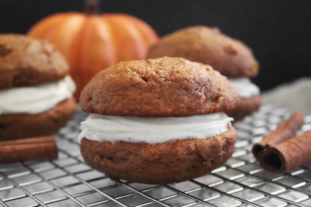 Pumpkin-spiced whoopie pies on a wire cooling rack, with cinnamon sticks visible in the foreground and a blurred pumpkin in the background