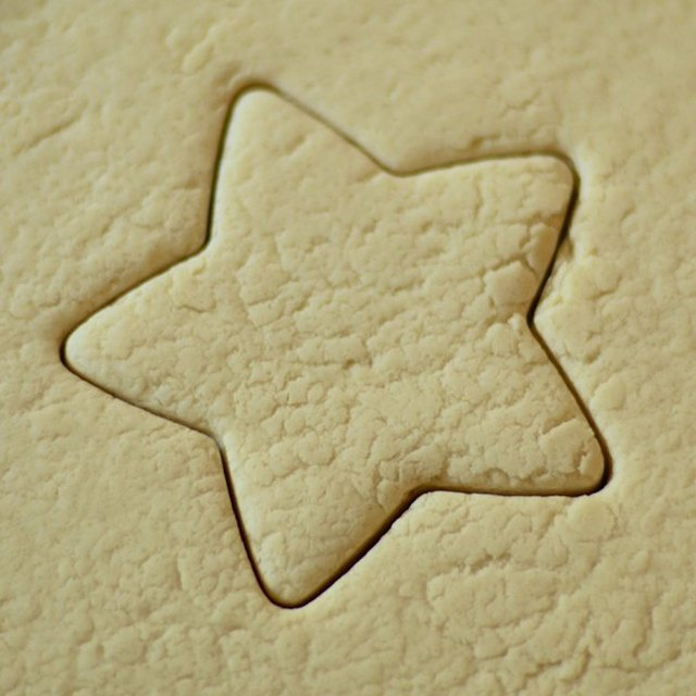 Closeup of rolled-out dough, centered on a star shape made with a cookie cutter