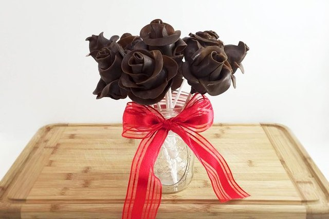 A vase on a wooden cutting board, tied with a red ribbon, containing a bouquet of dark Tootsie Roll roses.