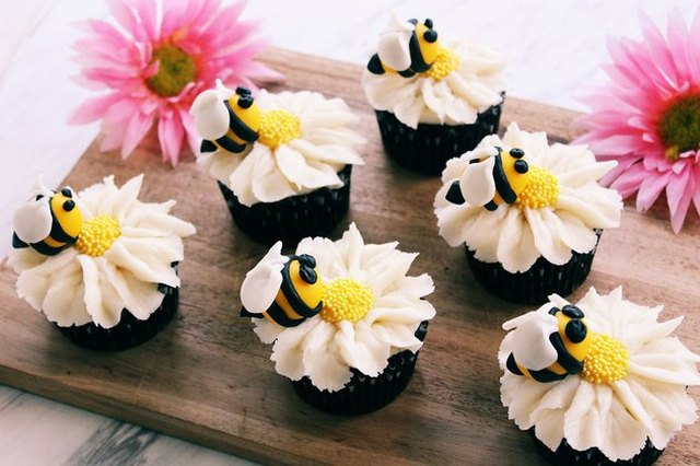 Cupcakes decorated with piped flowers and bumble bees, displayed on a cutting board with a pair of pink flower blossoms.