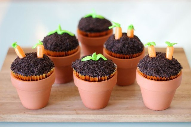 A set of six cupcakes in small terra cotta pots, with tops decorated to resemble baby plants in soil.