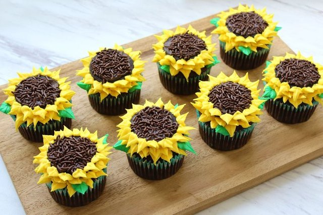 Eight cupcakes, decorated to look like sunflowers, arranged on a wooden cutting board on a marble counter top.