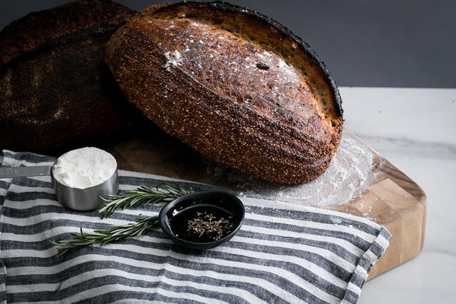 Loaf of bread with herbs and flour