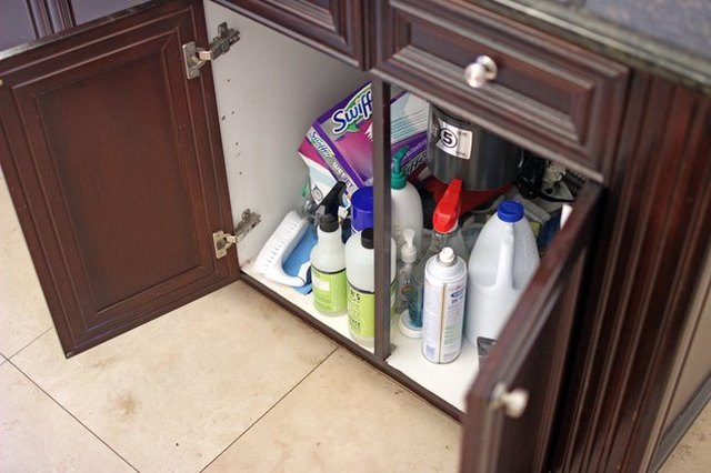 Photo of open cupboard doors, revealing a jumble of cleaning products and disinfectants.