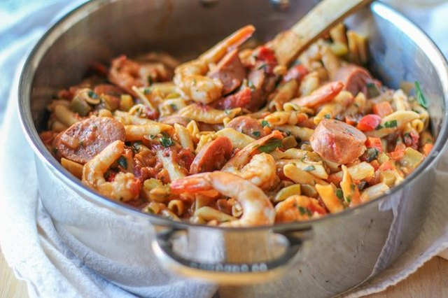 """Stainless steel pot full of """"gumbo"""" pasta on a stove top, stirred by a wooden spoon."""