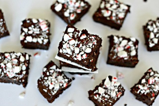 Overhead view of peppermint-topped brownies on a white work surface.