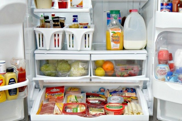 An open French-door, bottom-freezer refrigerator displaying its neatly organized contents.