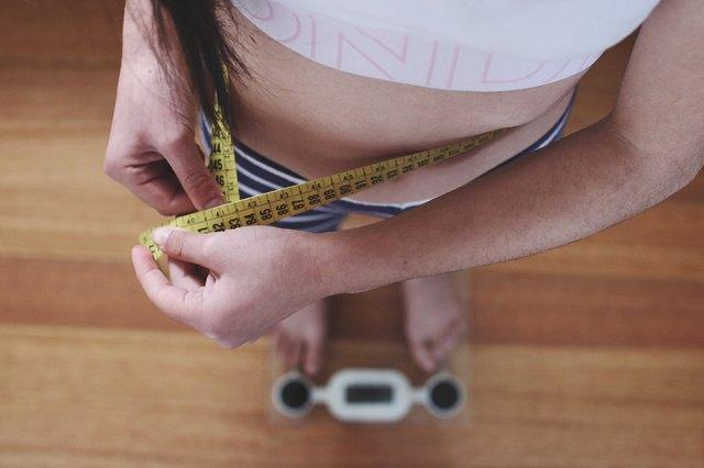 girl weighing herself and measuring waist