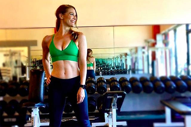 celebrity trainer Holly Perkins at a gym with dumbbells
