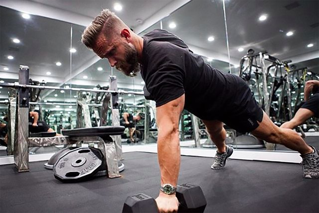 celebrity fitness trainer Magnus Lygdback works out at his gym with dumbbells