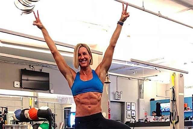 celebrity personal trainer Kira Stokes working out at a gym with kettlebells