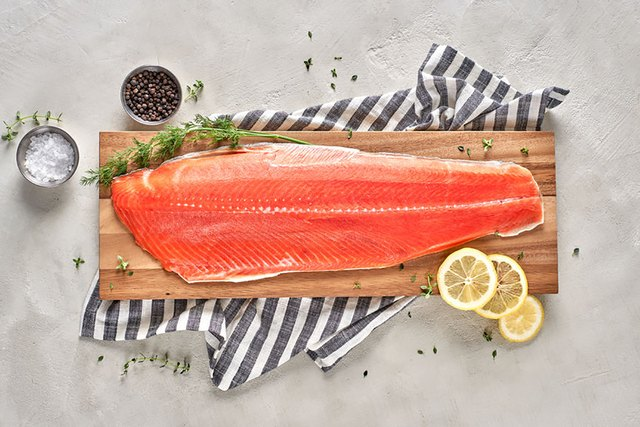 salmon filet with salt and lemon on cutting board