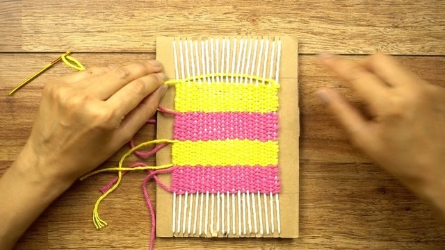 Cardboard loom with a handwoven coaster in progress
