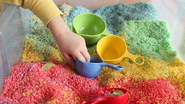 Child's hand explores an finished rainbow sensory box