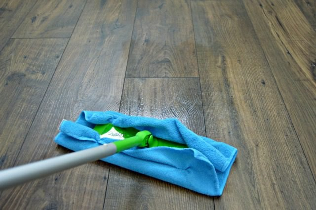 Microfiber towel attached to a Swiffer cleaning wood flooring