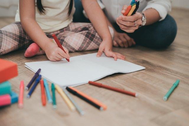 Woman And Girl Drawing On Hardwood Floor