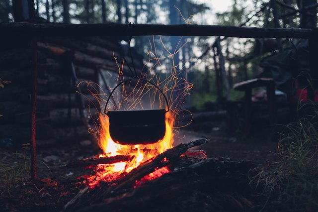 Container hanging over campfire in forest