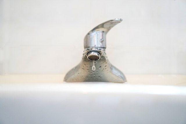 Close-Up Of Water Dripping From Faucet In Bathroom Sink