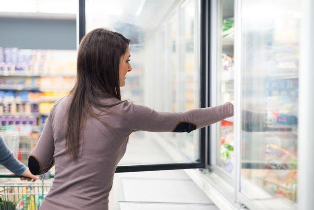 Woman taking deep frozen food from a freezer
