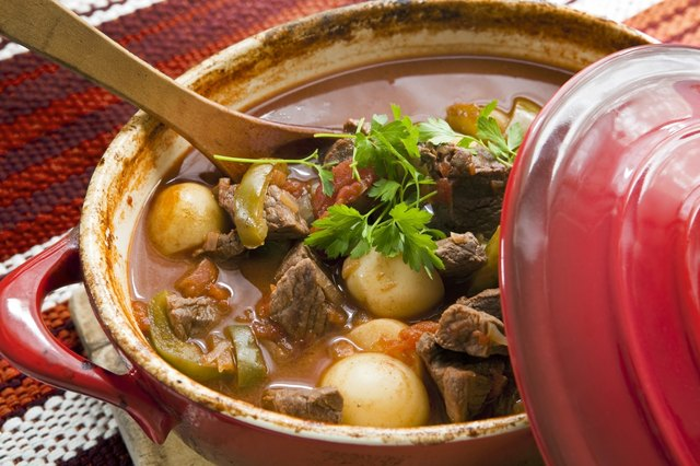 Red pot full of goulash with wooden spoon in it